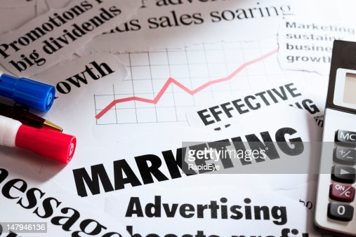 Marketing headlines with calculator, pens and sales graph : Stock Photo