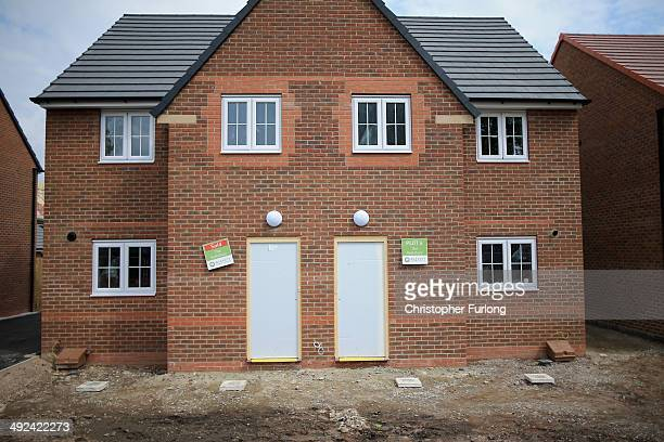 Marketing signs adorn the front of new homes on a housing development on May 20 2014 in Middlewich England Official figures have shown that house...