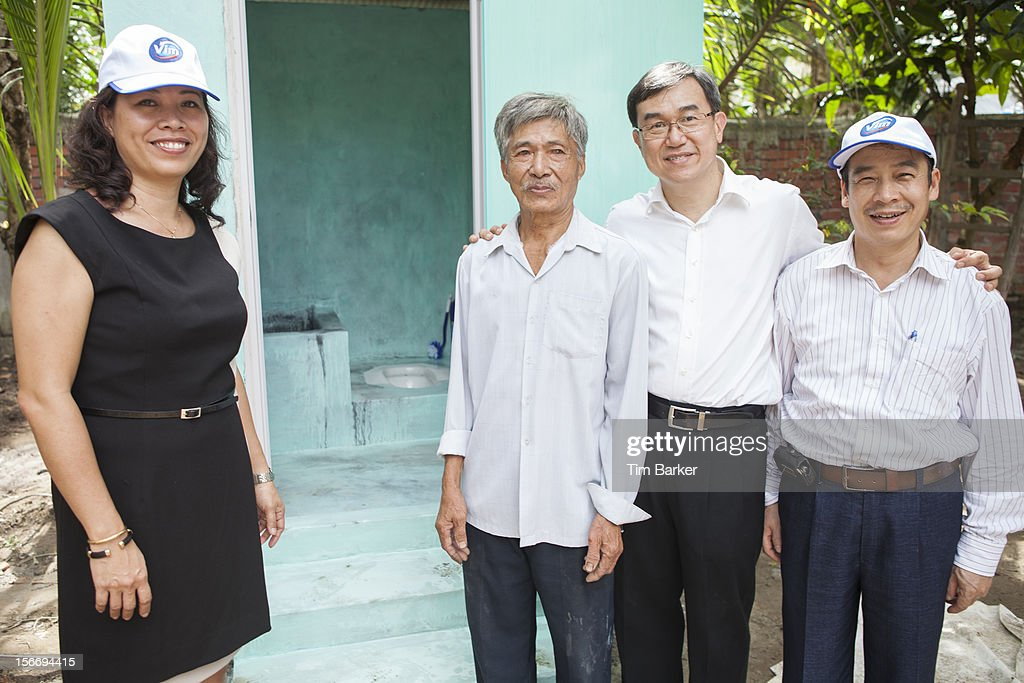 Marketing Vice President of Unilever Vietnam Nguyen Thi Bich Va, Mr. Nguyen Van Tu, CEO of World Toilet Organisation Jack Sim and Deputy Director of Environmental Management Department at the Vietnam Ministry of Health Tran Dac Phu pose infront of Nguyen Van Tu's new toilet which has been recently installed, on World Toilet Day on November 19, 2012 in Vinh Long, Vietnam.