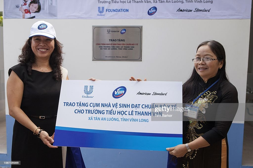 Marketing Vice President of Unilever Vietnam Nguyen Thi Bich Van and Principal of Le Thanh Van Primary School Ha Thi Dung hold a cheque at the inauguration of the new toilet complex at the Le Thanh Van Primary School on World Toilet Day on November 19, 2012 in Vinh Long, Vietnam.
