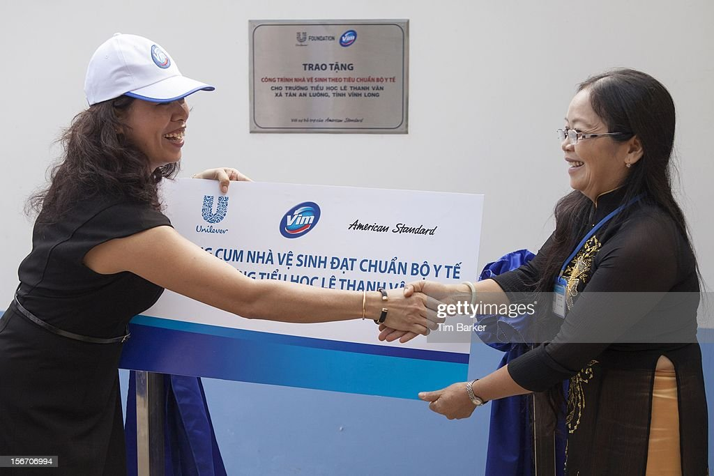 Marketing Vice President of Unilever Vietnam Nguyen Thi Bich Van and Principal of Le Thanh Van Primary School Ha Thi Dung shake hands at the inauguration of the new toilet complex at the Le Thanh Van Primary School on World Toilet Day on November 19, 2012 in Vinh Long, Vietnam.