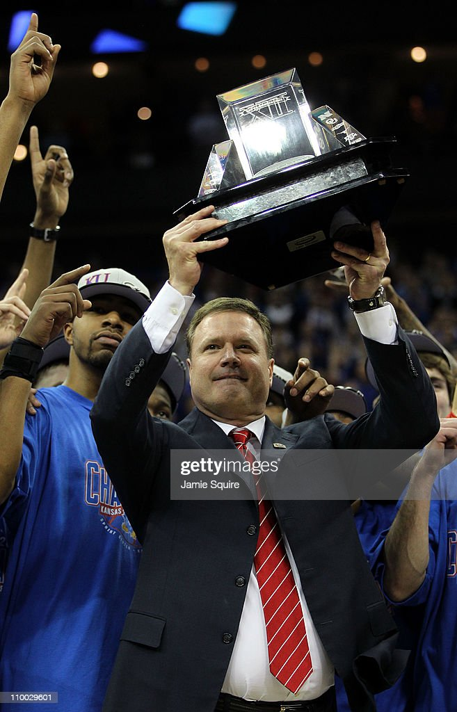 Markieff Morris and head coach Bill Self of the Kansas Jayhawks celebrate with the Big 12 championship trophy after defeating the Texas Longhorns...