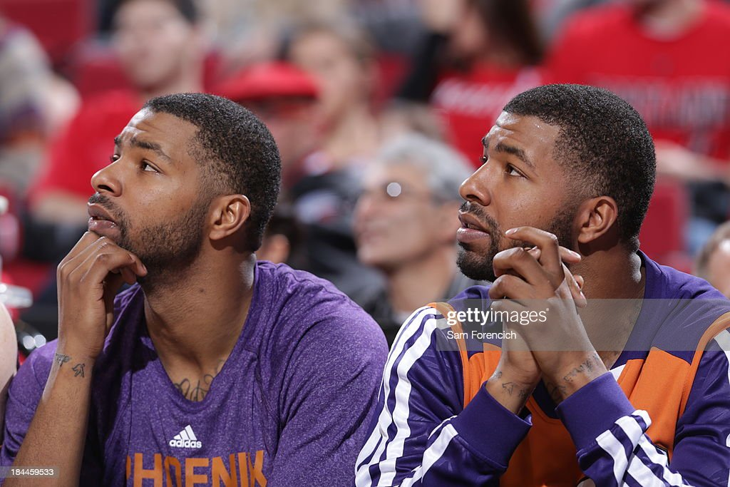 Markieff Morris #11 and Marcus Morris #15 of the Phoenix Suns sits on the bench during the game against the Portland Trail Blazers on October 9, 2013 at the Moda Center Arena in Portland, Oregon.
