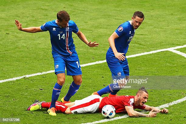 Marko Arnautovic of Austria goes down under the challenge of Gylfi Sigurdsson of Iceland and ice 14 during the UEFA EURO 2016 Group F match between...