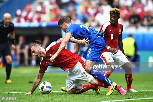 Marko Arnautovic of Austria goes down under the challenge of Kari Arnason of Iceland during the UEFA EURO 2016 Group F match between Iceland and...