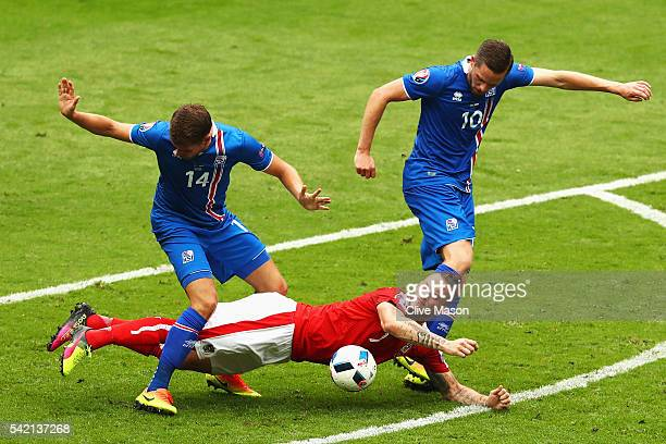 Marko Arnautovic of Austria goes down under the challenge of Kari Arnason of Iceland and Gylfi Sigurdsson of Iceland during the UEFA EURO 2016 Group...