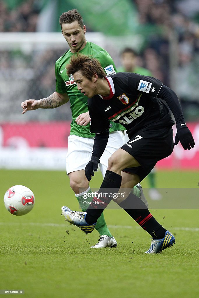 Marko Arnautovic (L) of Bremen and Ja Cheol Koo (R) of Augsburg battle for the ball during the Bundesliga match between SV Werder Bremen and FC Augsburg at Weser Stadium on March 2, 2013 in Bremen, Germany.