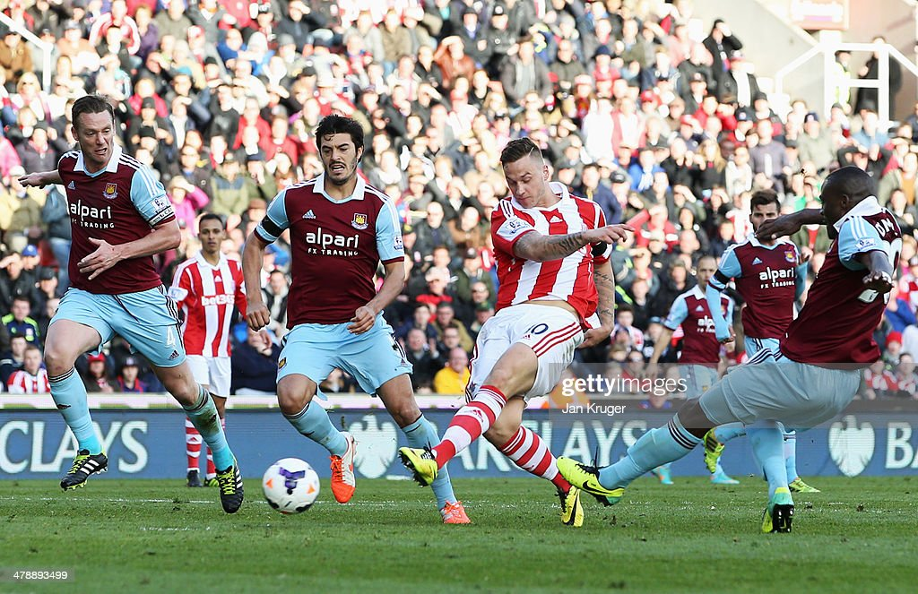 Marko Arnautovic of Stoke City beats Kevin Nolan (L), James Tomkins (2L) and Guy Demel of West Ham United (R) to score their second goal during the Barclays Premier League match between Stoke City and West Ham United at Britannia Stadium on March 15, 2014 in Stoke on Trent, England.