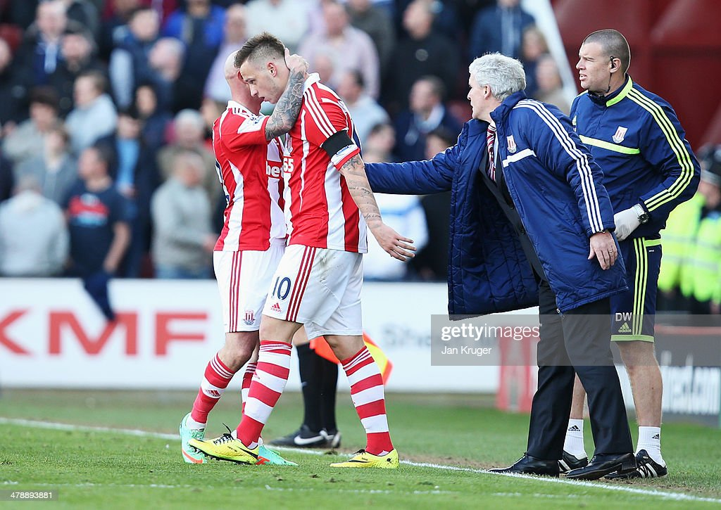 Marko Arnautovic of Stoke City (2L) celebrates with Stephen Ireland and manager Mark Hughes as he scores their second goal during the Barclays Premier League match between Stoke City and West Ham United at Britannia Stadium on March 15, 2014 in Stoke on Trent, England.