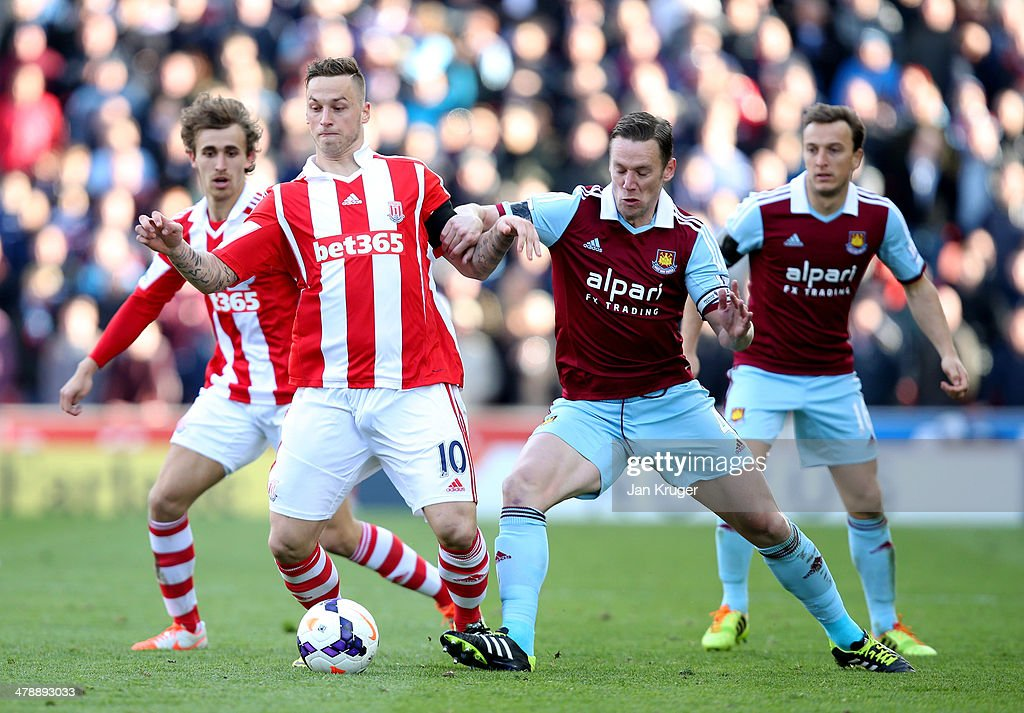Marko Arnautovic of Stoke City holds off Kevin Nolan of West Ham United during the Barclays Premier League match between Stoke City and West Ham United at Britannia Stadium on March 15, 2014 in Stoke on Trent, England.
