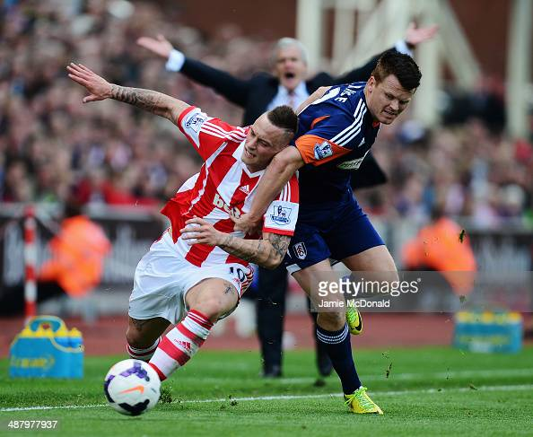 Marko Arnautovic of Stoke City is challenged by John Arne Riise of Fulham as Stoke City manager Mark Hughes appeals in the background during the...
