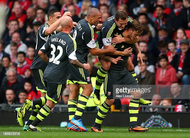 Marko Arnautovic of Stoke City is mobbed by team mates after scoring his goal from a free kick during the Barclays Premier League match between...