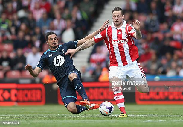 Marko Arnautovic of Stoke City is tackled by Nacer Chadli of Tottenham Hotspur during the Barclays Premier League match between Stoke City and...