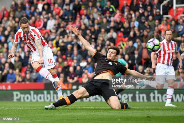 Marko Arnautovic of Stoke City scores his sides first goal as Harry Maguire of Hull City attempts to block during the Premier League match between...