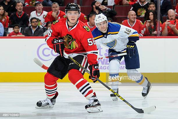 Marko Dano of the Chicago Blackhawks and Ty Rattie of the St Louis Blues watch for the puck in the first period of the NHL game at the United Center...