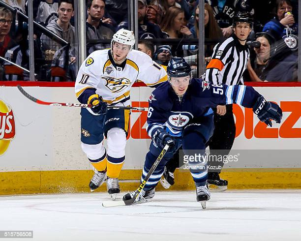 Marko Dano of the Winnipeg Jets and Colton Sissons of the Nashville Predators follow the play down the ice during second period action at the MTS...