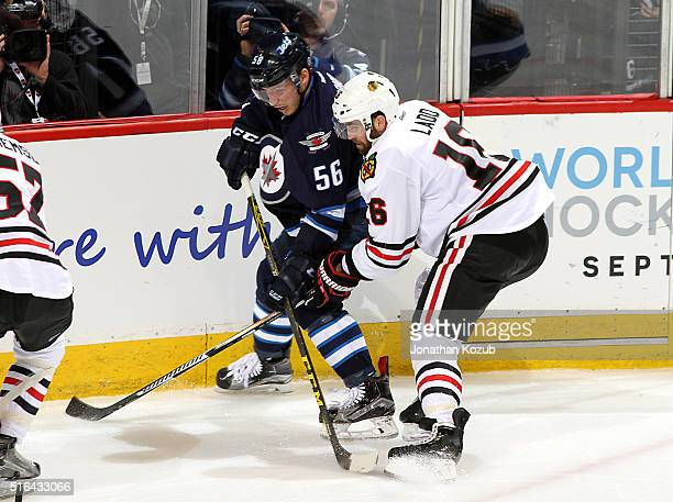 Marko Dano of the Winnipeg Jets battles Andrew Ladd of the Chicago Blackhawks as they keep an eye on the play during second period action at the MTS...