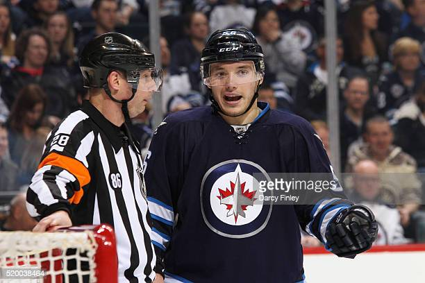 Marko Dano of the Winnipeg Jets discusses play with referee Chris Lee during a third period stoppage in play against the Minnesota Wild at the MTS...