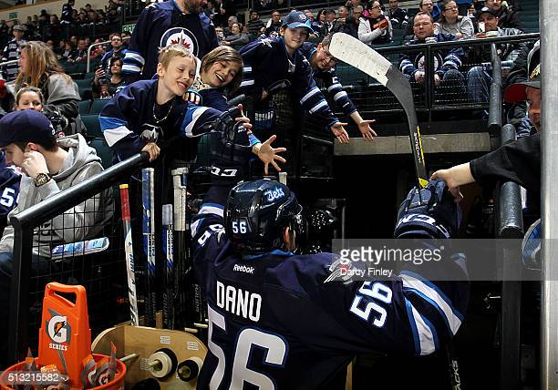 Marko Dano of the Winnipeg Jets high fives fans as he leaves the ice following the pregame warm up prior to NHL action against the Florida Panthers...