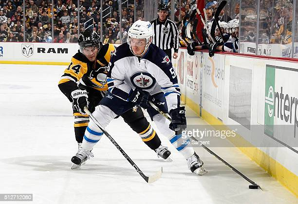 Marko Dano of the Winnipeg Jets looks to pass the puck in front of Chris Kunitz of the Pittsburgh Penguins at Consol Energy Center on February 27...