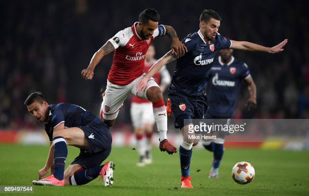 Marko Gobeljic of FK Crvena Zvezda and Damien Le Tallec of FK Crvena Zvezda battle for possession with Theo Walcott of Arsenal during the UEFA Europa...