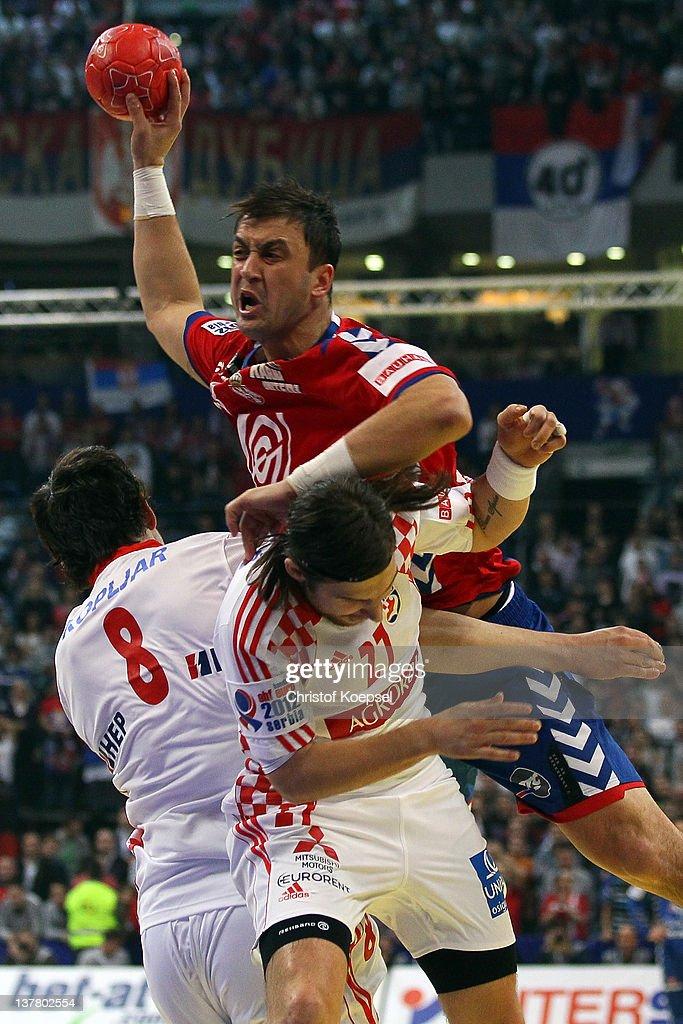 Marko Kopljar and Ivan Cupic of Croatia defend against Momir Ilic of Serbia during the Men's European Handball Championship second semi final match...