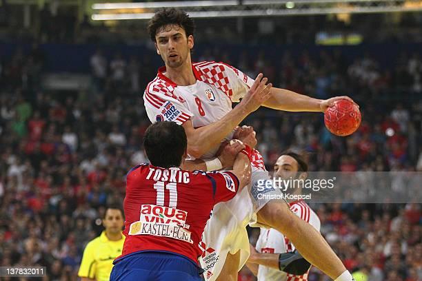 Marko Kopljar of Croatia shoots over Alem Toskic of Serbia during the Men's European Handball Championship second semi final match between Serbia and...