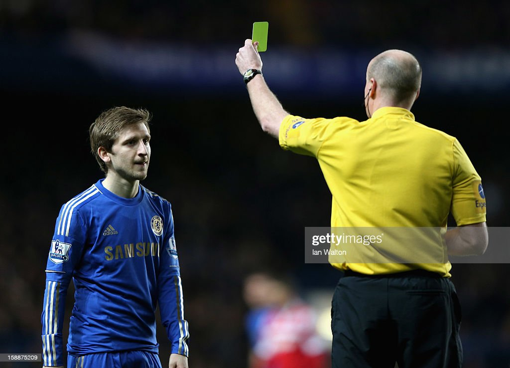 Marko Marin of Chelsea is shown a yellow card by referee Lee Mason after a strong tackle on Stephane Mbia of Queens Park Rangers during the Barclays Premier League match between Chelsea and Queens Park Rangers at Stamford Bridge on January 2, 2013 in London, England.
