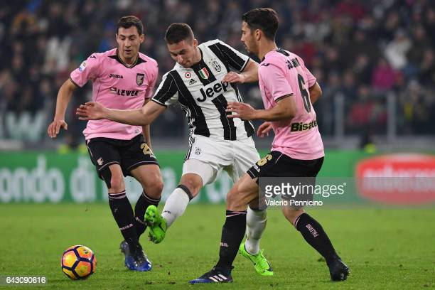 Marko Pjaca of Juventus FC is challenged by Mato Jajalo and Edoardo Goldaniga of US Citta di Palermo during the Serie A match between Juventus FC and...