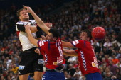 Marko Vujin and Momir Ilic of Serbia defend against Lars Kaufmann of Germany during the Men's European Handball Championship second round group one...
