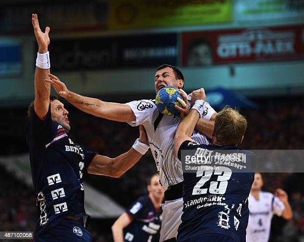 Marko Vujin of Kiel is challenged by Tobias Karlsson and Henrik Toft Hansen of Flensburg during the DKB Handball Bundeslga match between SG...