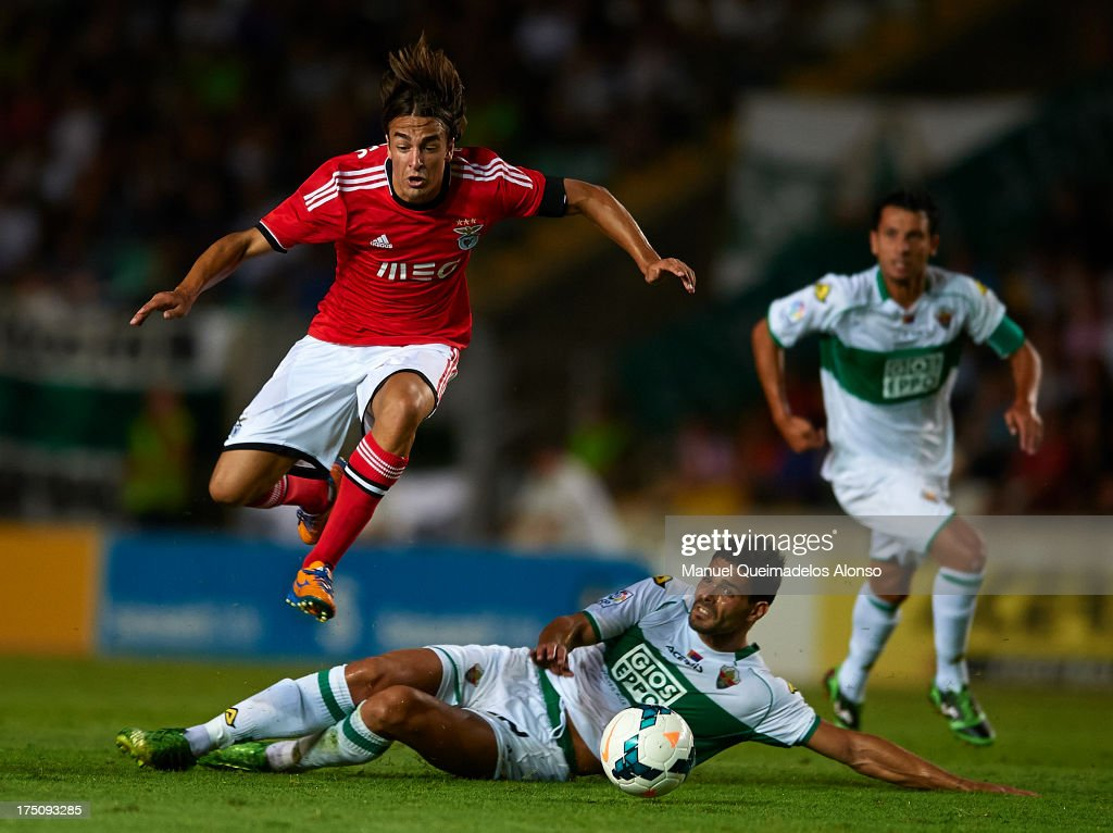 Markovic (L) of Benfica is tackled by Botia of Elche during a friendly match between Elche CF and Benfica at Estadio Martinez Valero on July 31, 2013 in Elche, Spain.