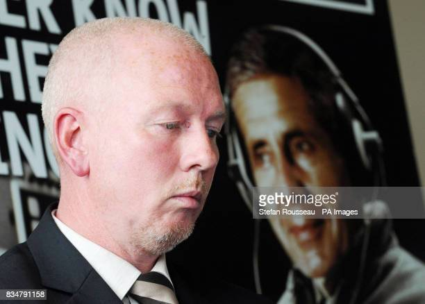 Marks and Spencer employee Tony Goode sits in front of a picture of Marks and Spencer Chief Executive Stuart Rose during a news conference held by...