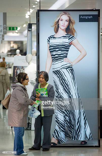 A Marks Spencer's employee right talks with a customer near an advert for the company's 'Autograph' clothing range inside a retail store operated by...