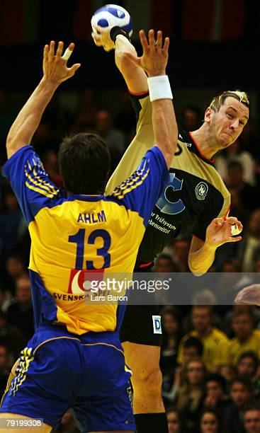 Markus Ahlm of Sweden in action with Pascal Hens of Germany during the Men's Handball European Championship main round Group II match between Germany...