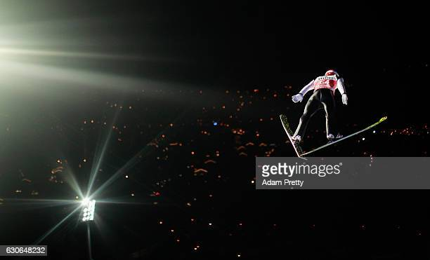 Markus Eisenbbichler of Germany soars through the air during his qualification jump on Day 1 of the 65th Four Hills Tournament ski jumping event on...