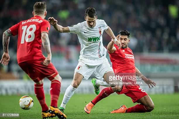 Markus Feulner of Augsburg is challenged by Emre Can of Liverpool during the UEFA Europa League Round of 32 first leg match between FC Augsburg and...