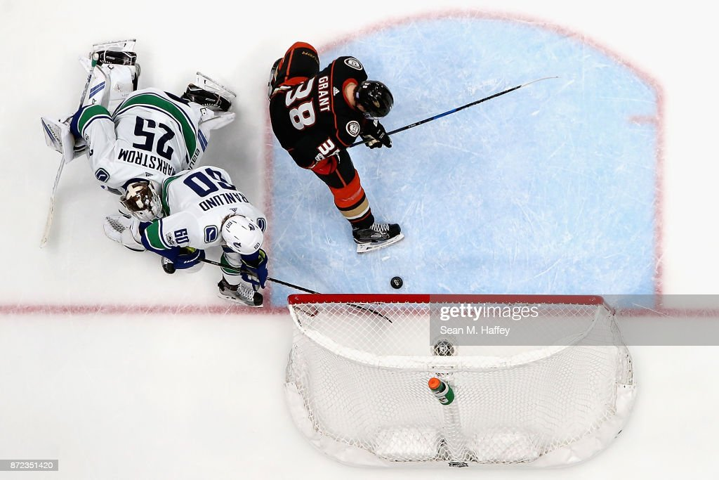 Markus Granlund #60 and Jacob Markstrom #25 of the Vancouver Canucks defend against Derek Grant #38 of the Anaheim Ducks during the third period of a game at Honda Center on November 9, 2017 in Anaheim, California.