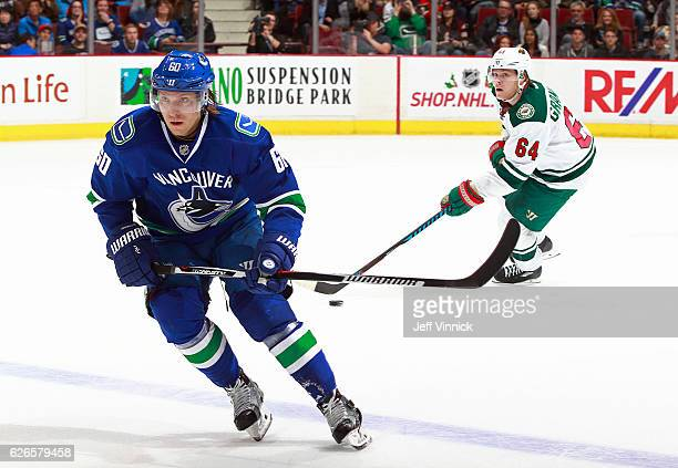 Markus Granlund of the Vancouver Canucks skates up ice as his brother Mikael Granlund of the Minnesota Wild skates up ice behind him with the puck...
