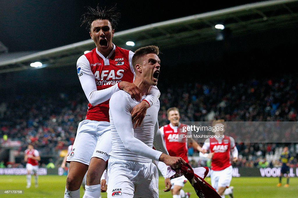 Markus Henriksen of AZ celebrates scoring the winning goal in the final minute of the game as Steven Berghuis jumps on his back during the Dutch...
