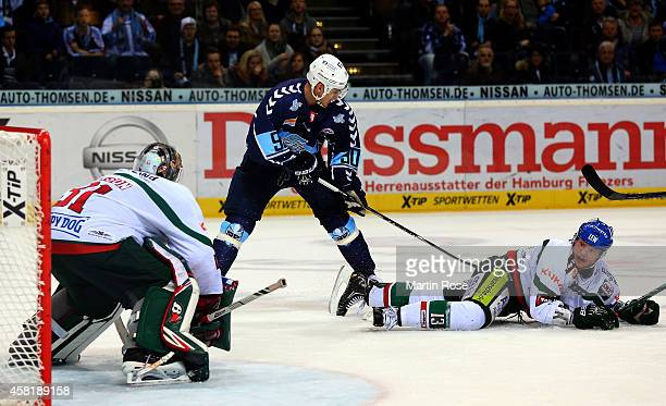 Markus Keller goaltender of Augsburg makes a save on Jerome Flaake of Hamburg during the DEL game between Hamburg Freezers and Augsburger Panther on...