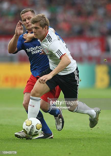 Markus Kurth of Windeck challenges Toni Kroos of Bayern during the DFB Cup first round match between TSV G Windeck and FC Bayern Muenchen at...