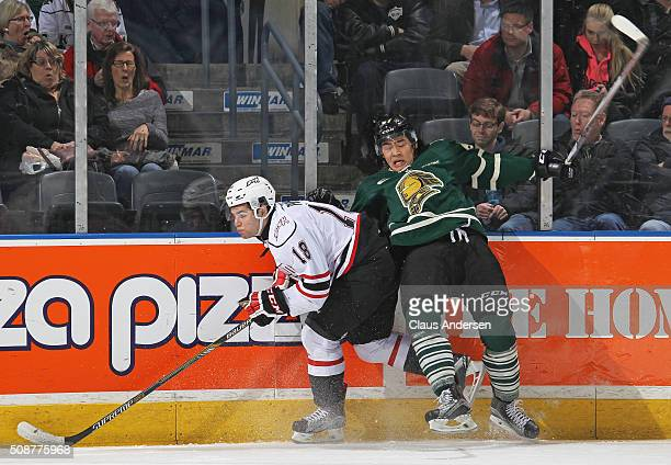 Markus Phillips of the Owen Sound Attack battles against Kole Sherwood of the London Knights during an OHL game at Budweiser Gardens on February 5...