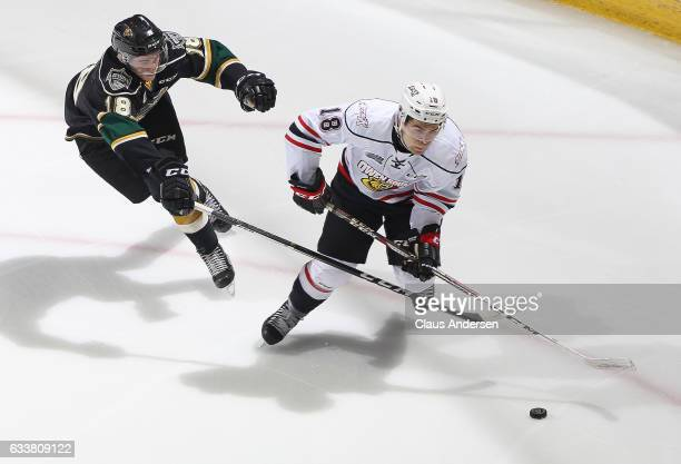 Markus Phillips of the Owen Sound Attack skates away from a checking Liam Foudy of the London Knights during an OHL game at Budweiser Gardens on...