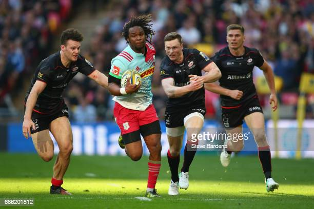 Marland Yarde of Harlequins breaks away from Chris Ashton and Duncan Taylor of Saracens during the Aviva Premiership match between Saracens and...