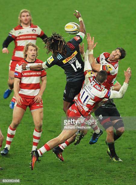 Marland Yarde of Harlequins jumps for the ball with James Hook and Jonny May of Gloucester during the Aviva Premiership Big Game 9 match between...