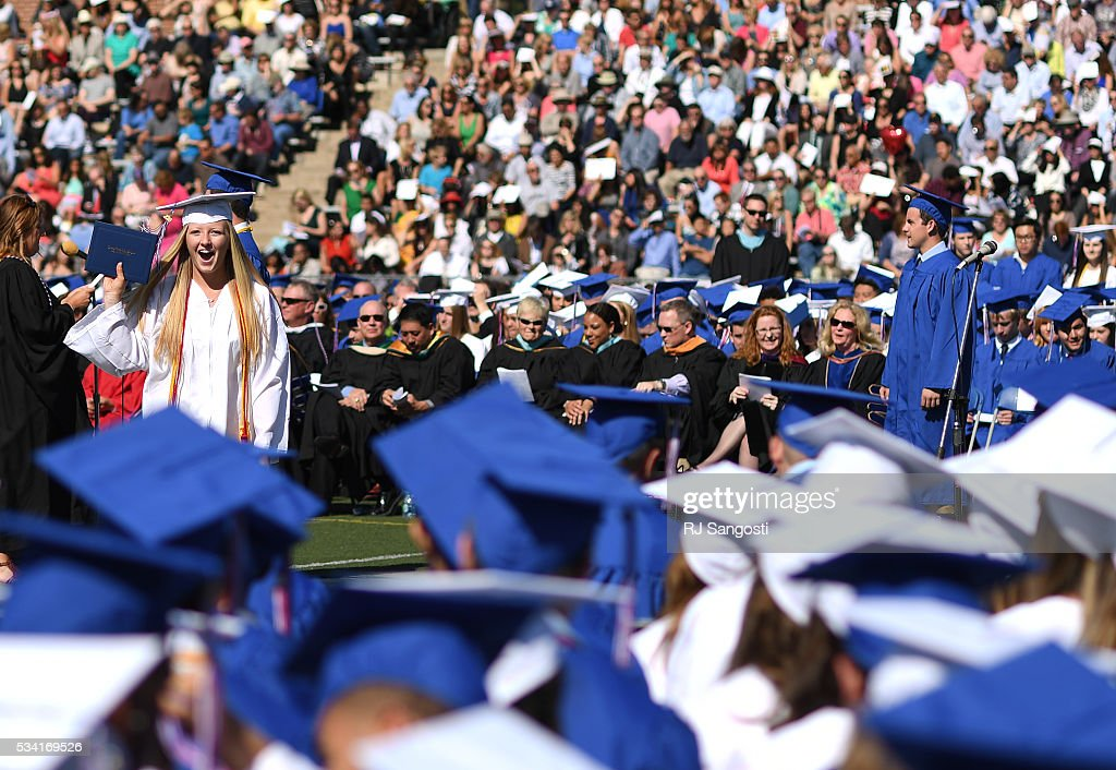 Marlena McClellan, 17, holds up her diploma during Cherry Creek High School graduation at Stutler Bowl, May 25, 2016. This is the school's sixty-first annual commencement.