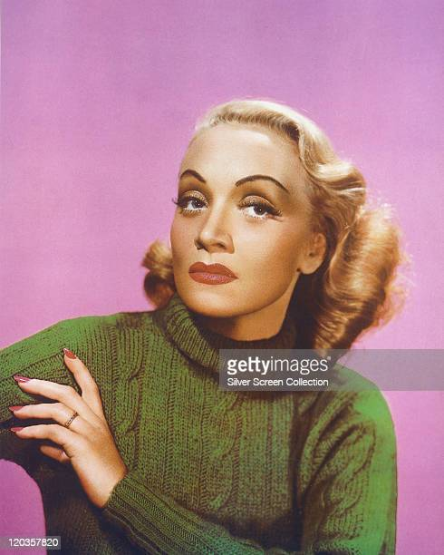Marlene Dietrich German actress and singer wearing a green polo neck jumper in a studio portrait against a pink background circa 1940