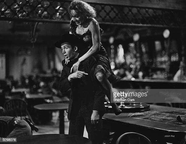 Marlene Dietrich leaps onto the back of James Stewart in a scene from the classic western 'Destry Rides Again' Alternatively titled 'Justice Rides...