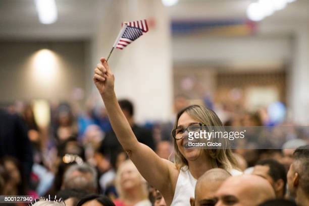 Marlene Mann of Brazil celebrates her country's name being called during the US Citizenship and Immigration Services naturalization proceeding at the...